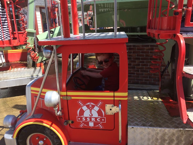 Little boy sitting in a fire engine on a ride