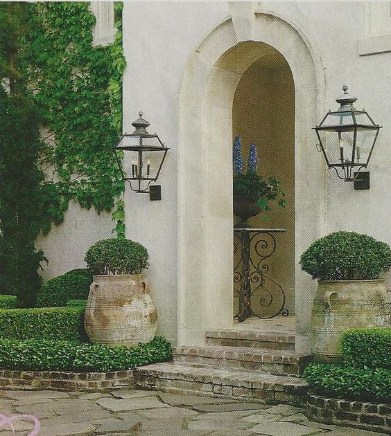 French country home exterior with antique pots.
