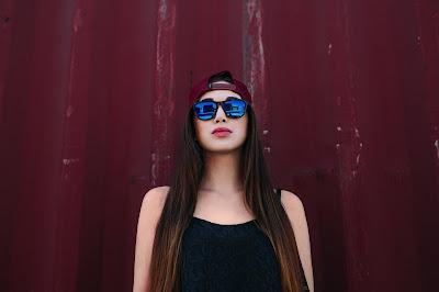 Chica con gafas y gorra roja mirando a cámara con fondo rojo