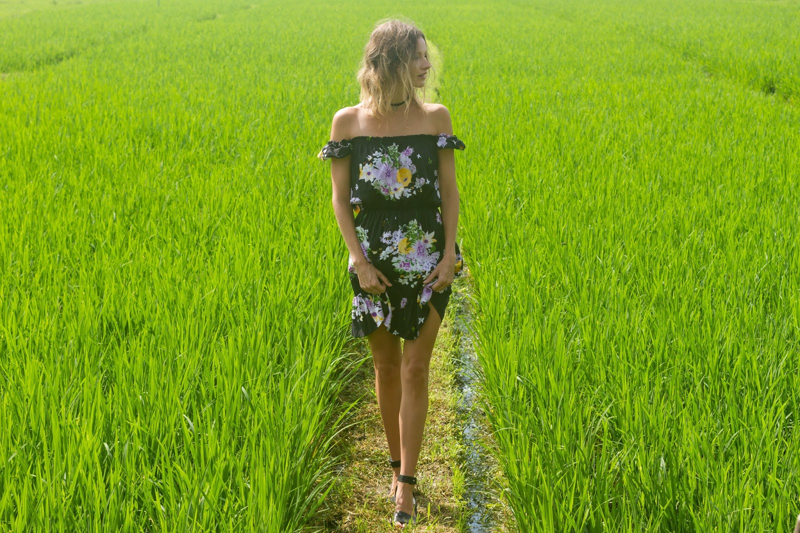 fashion and travel blogger, Alison Hutchinson, i s wearing the KAYVALYA Rosie Off The Shoulder Dress in Black Floral in a rice field in Bali