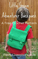 A boy in a red shirt is wearing a crocheted green backpack.  There is wooden fence in the background.  The boy's face is hidden.