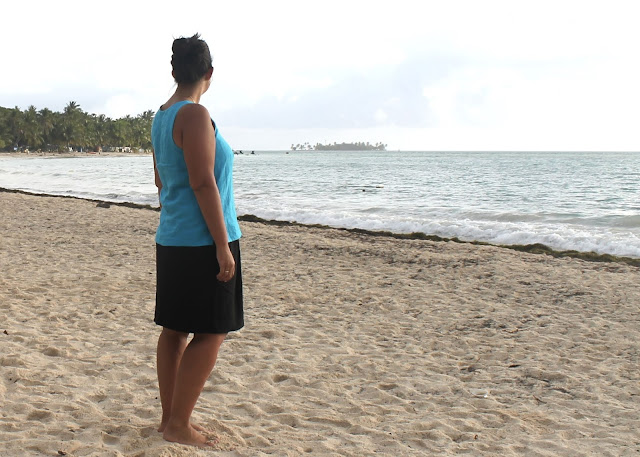 Woman standing on the sand looking at the sea, wearing a turquoise linen tank top hacked from the free Colette Sorbetto sewing pattern.