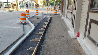 sidewalk work continues in front of the Berry Building
