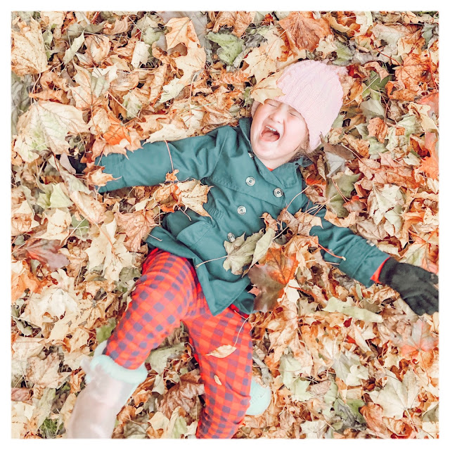little girl lying in leaves happy