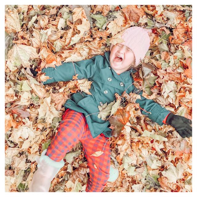 little girl lying in leaves happy