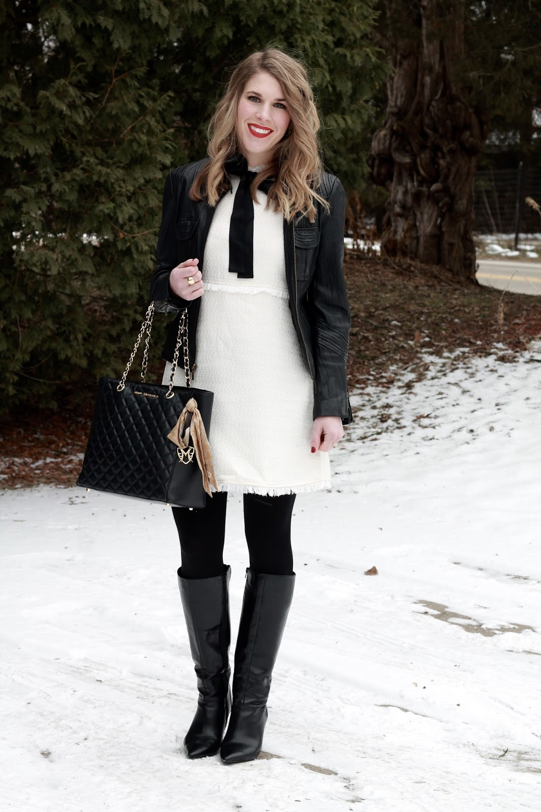 white tweed dress with black bow tie, leather moto jacket, black boots, black quilted tote
