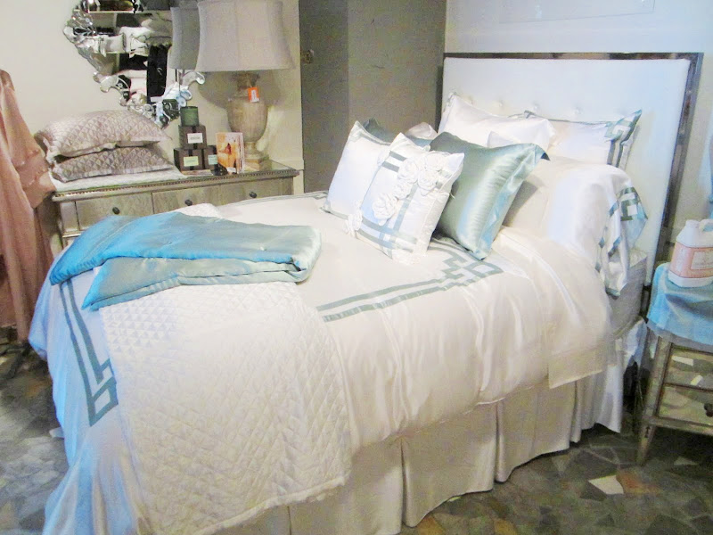 Bed with blue and white silk bedding by Kumi Kookoon