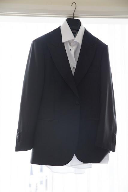 The groom's tuxedo hangs in the window | Karen Hill Photography