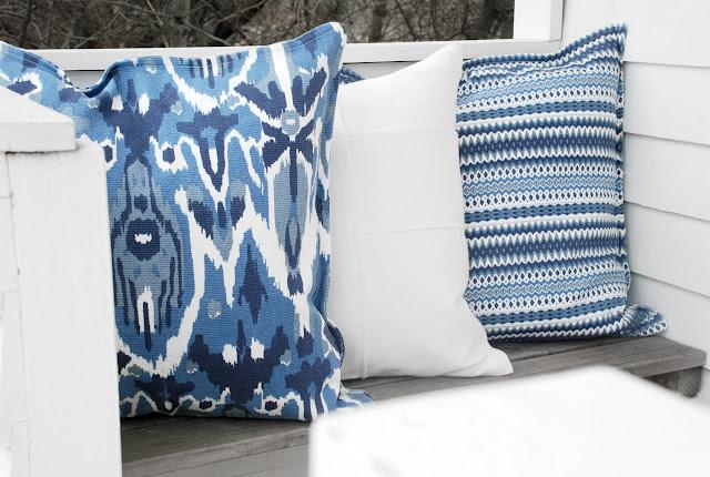 Ikat kudde och blå och vitrandig kudde i badhytt.