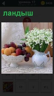 На столе в вазе стоит букет с ландышами и фрукты в тарелке на белой скатерти