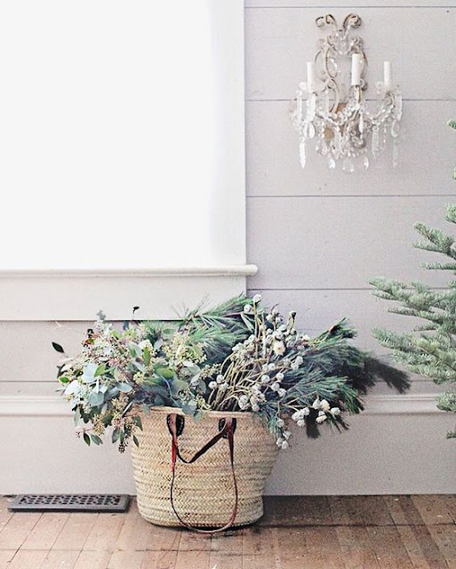 French farm basket with winter greenery and berries in farmhouse holiday decorating vignette