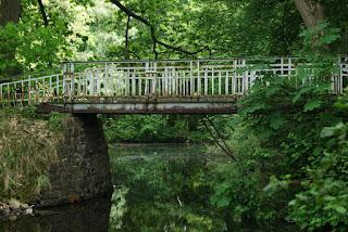 Eine etwas rostige Brücke führt etwas verwunschen über einen See