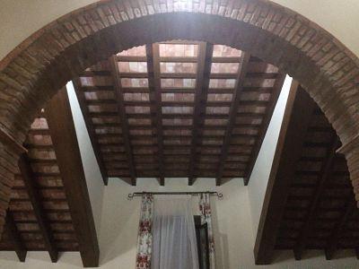 arco de ladrillo rústico y techo por tablas.