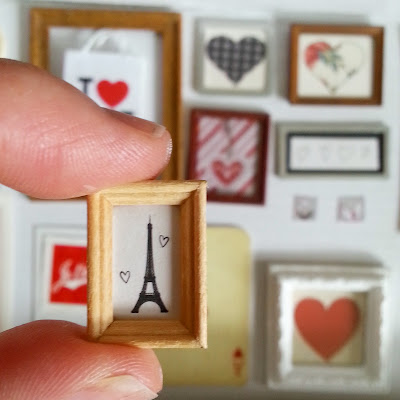 Modern miniature framed sketch of the Eiffel tower being held between thumb and finger in front of a selection of one-twelfth scale miniature framed pictures of hearts.