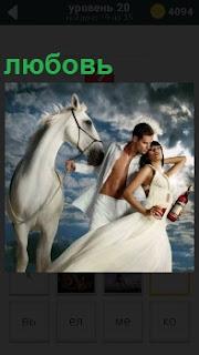 Мужчина и женщина обнимаются рядом с лошадью, показывая свою любовь друг к другу. Мужчина за поводья держит лошадь