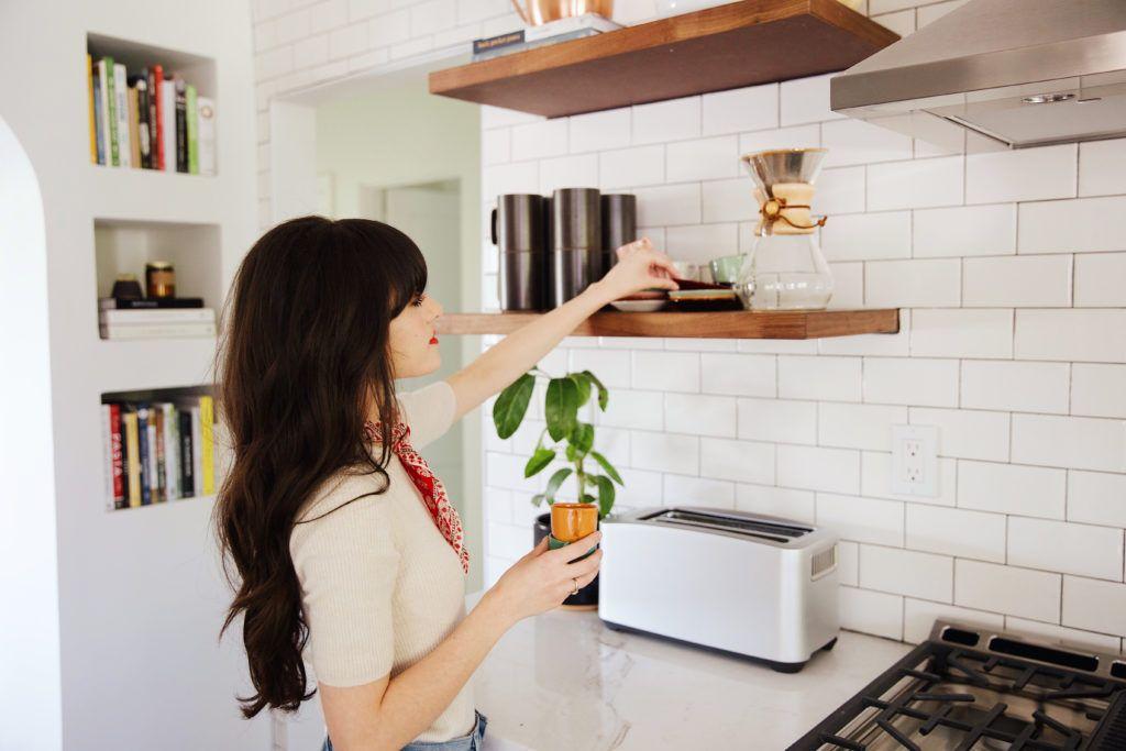 Wanita mengatur tempat penyimpanan di dapur rumah (newdarlings.com)
