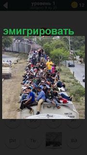На крыше поезда находятся люди в большом количестве, эмигрируют в другую местность