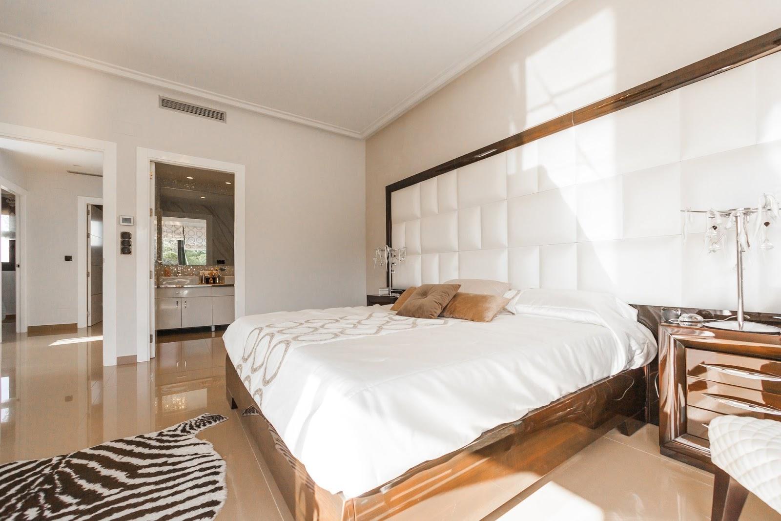Białe łóżko w drewnianobiałej sypialni