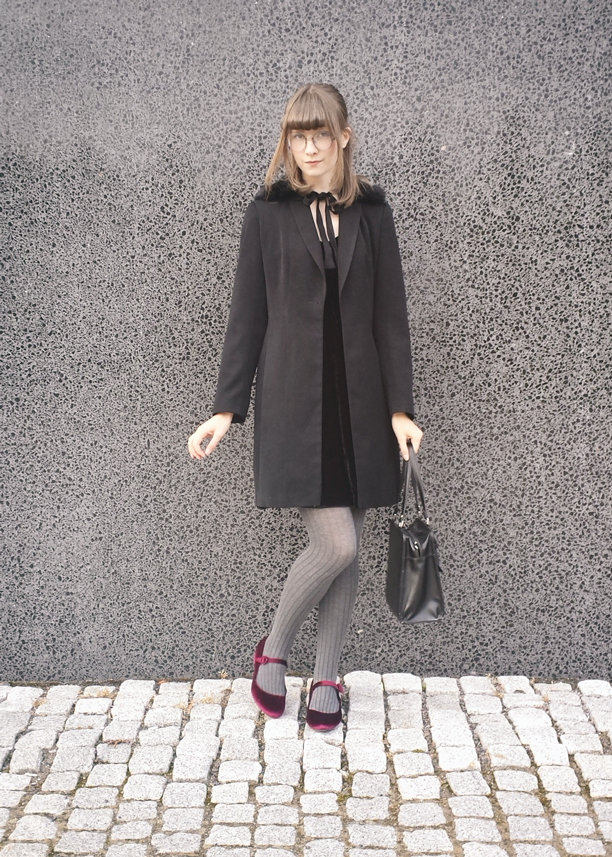 a Brown haired girl, leaning on a grey, textured wall. She is wearing a faux fur tippet, a semi long black coat, grey tights and wine red mary janes.