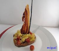 Barca de Tosta de pan de cereales con revuelto de patata,cebolla,chistorra y vela de beicón