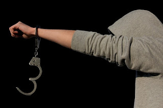 man in hoodie holds out hand, locked cuffs hanging from the wrist