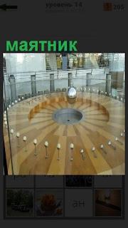 Круглый стол с шариками. Происходит колебания маятника, механические колебания