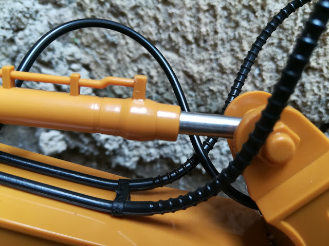 The Arm - is made in solid plastic with artificial hydraulic hose and cylinder.