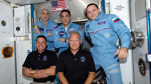 Demo-2 astronauts Bob Behnken and Doug Hurley take a group photo with Expedition 63 crew members Anatoly Ivanishin, Chris Cassidy and Ivan Vagner aboard the International Space Station.