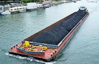 Denizde, kömür, asfalt veya başka siyah bir toprak taşıyan bir mavna