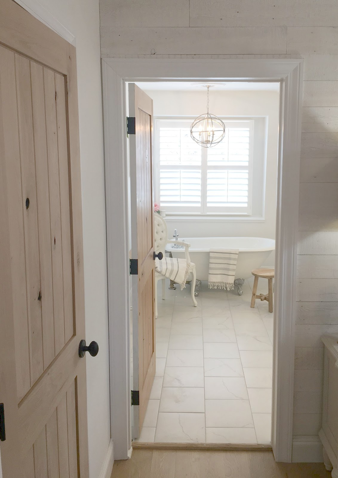 White Bathroom with vintage style and clawfoot tub by Hello Lovely Studio. #bathroom #vintage #alderdoor #clawfoottub