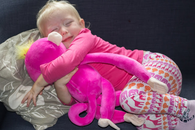 A toddler lying down and hugging the Fingerlings HUGS soft toy