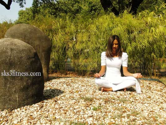 A girl meditating in Jal Shamak mudra on ground of Garden in sunlight