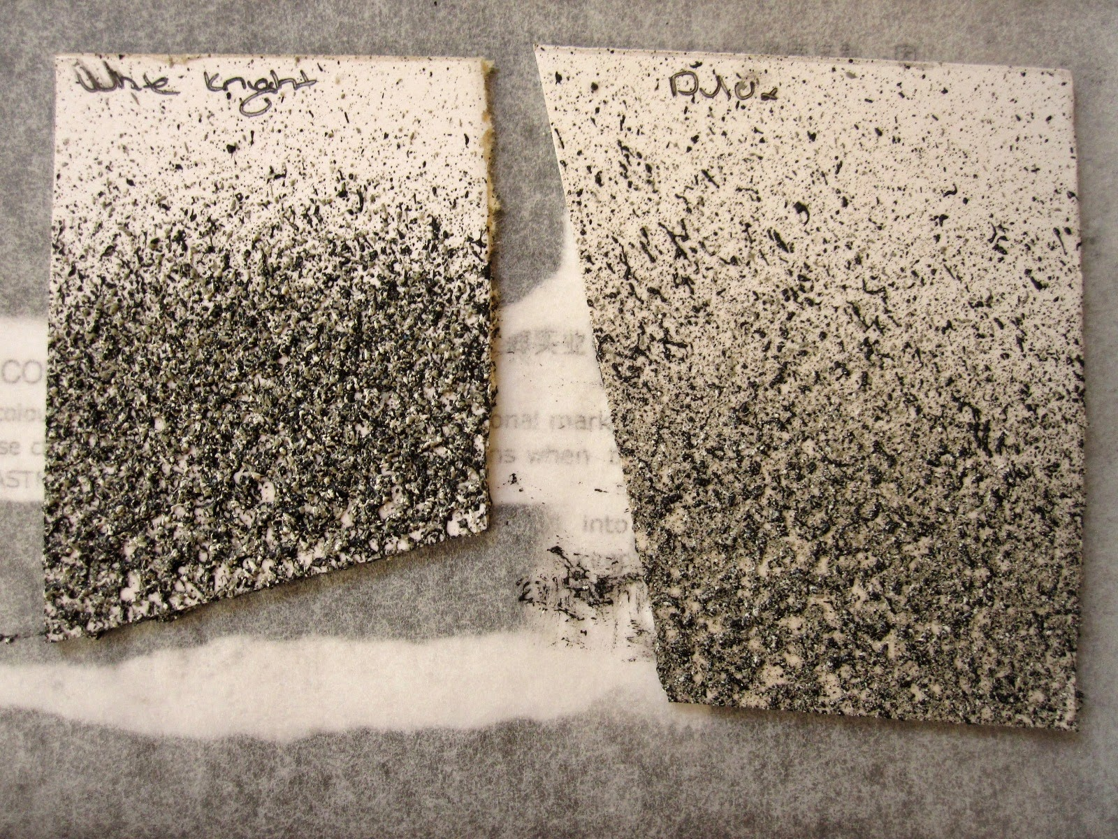 Two sample pieces of carboard, painted with different brands of concrete-looking paint.