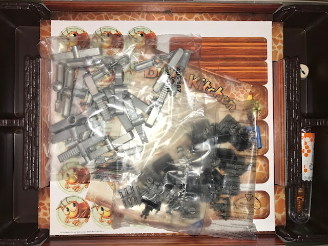 View inside the box when first opened. The cutlery is in two parts and in bags and the sheet of counters and trap covers is visible underneath