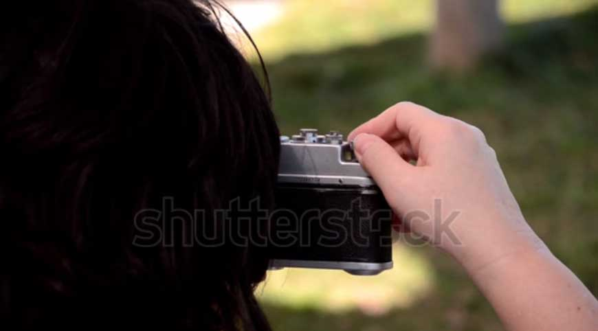 Woman takes pictures through the viewfinder of an old analog camera