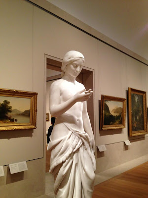 Marble statue of a man looking down at his hand in front of him holding something--could be a phone, but it's a cross
