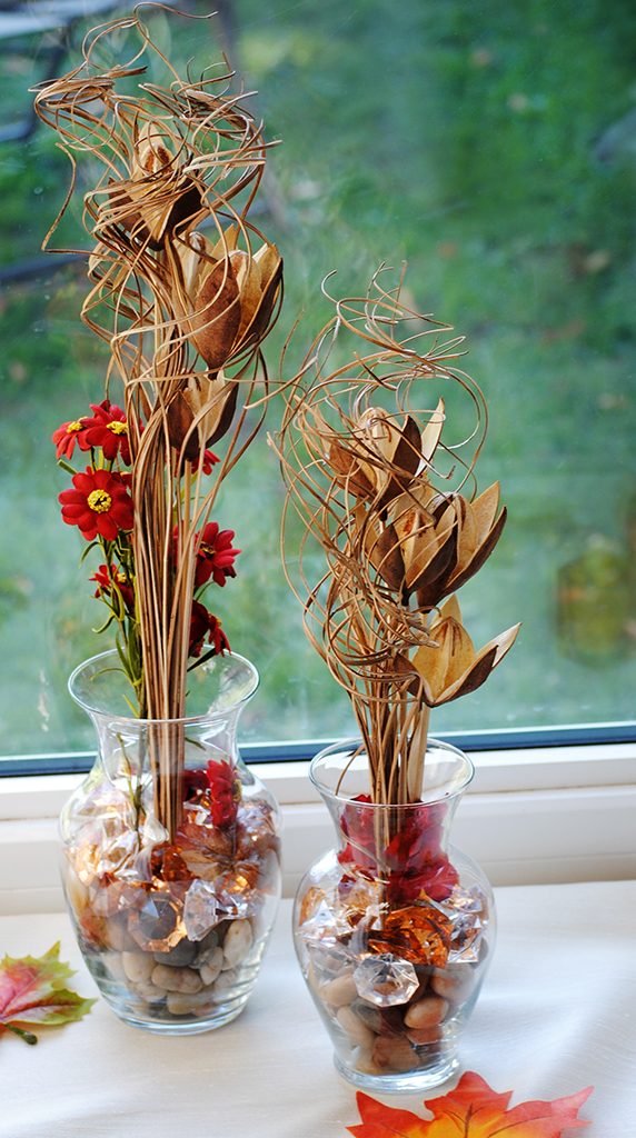 A fall window display of tall glass vases with dried rushes, and orange leaves.
