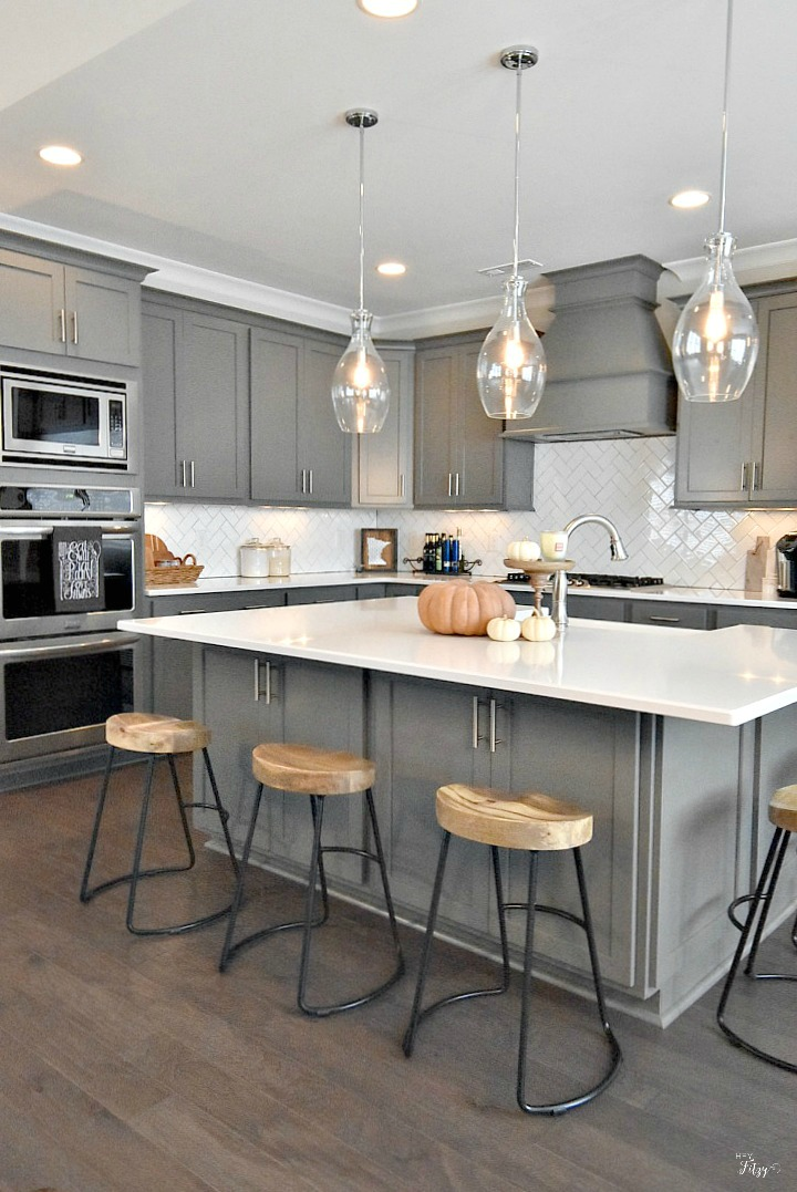 Southern style modern home kitchen with wood floors, gray cabinets, stainless steel appliances, and an amazing backsplash.