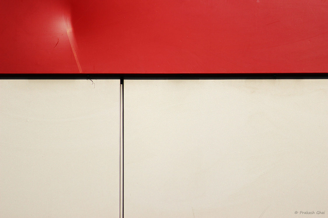 A minimalist photo of A small dent on a red metal sheet indicating a little blip in a relationship.