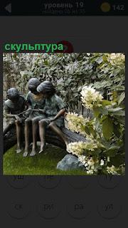 В саду около деревьев сделана скульптура детей сидящих на дереве