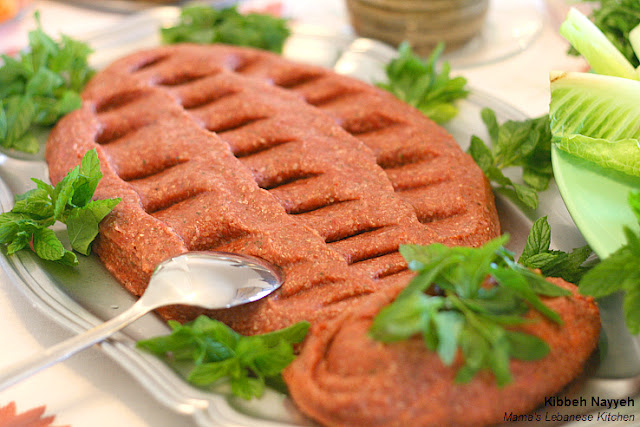 Kibbeh Nayyeh in a serving tray and spoon garnished with mint leaves