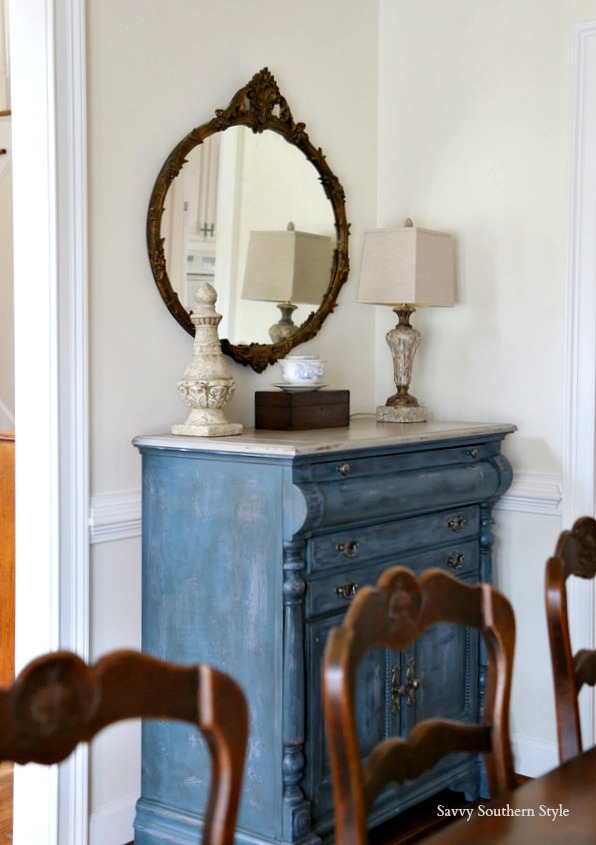 Antique mirror over painted blue dining buffet