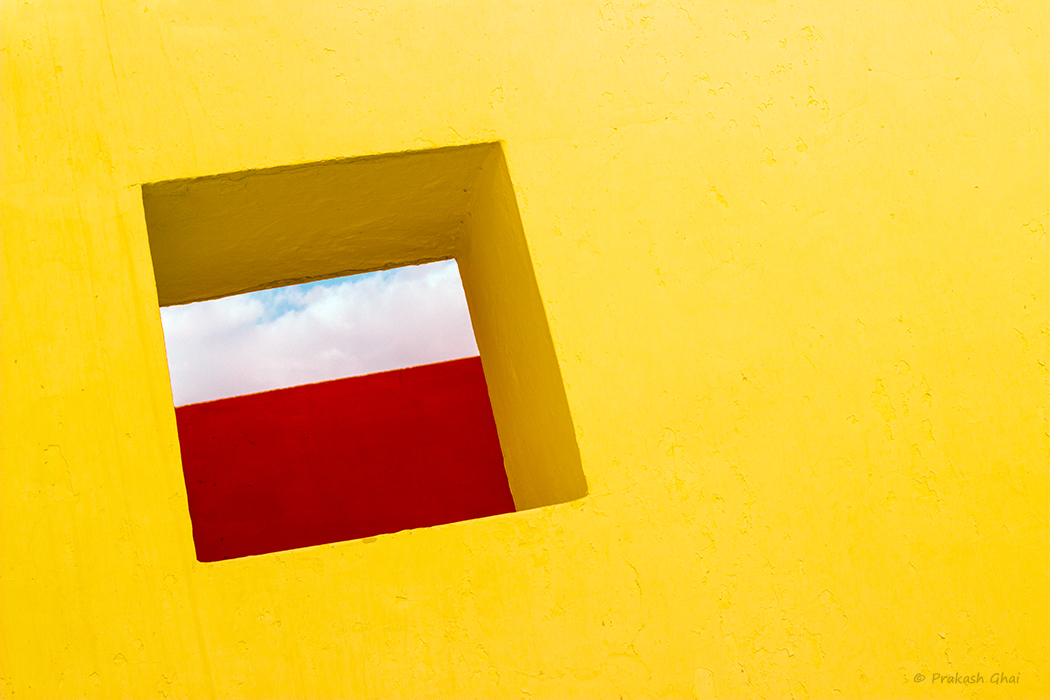 A Minimalist Photo of Yellow wall with a sqaure opening
