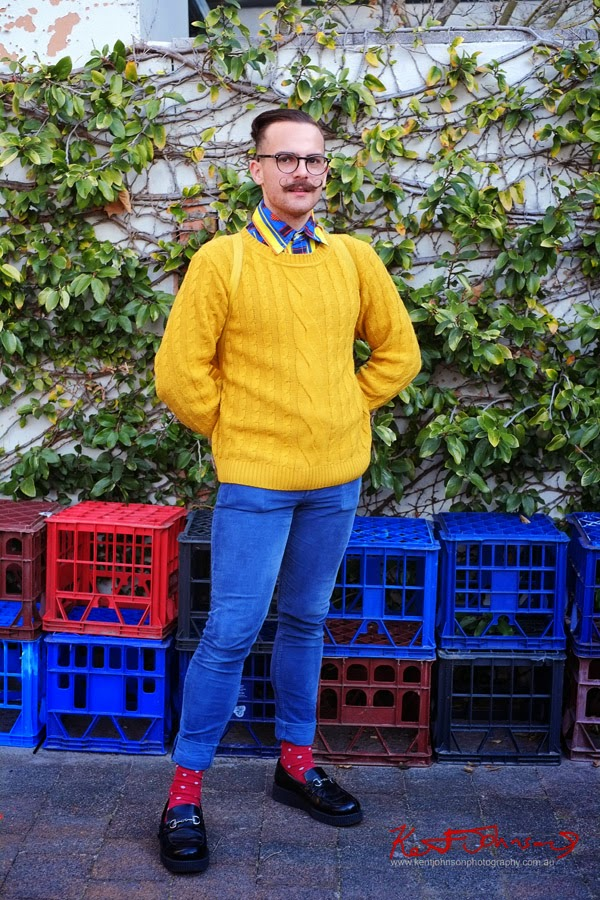 Men's Style - Yellow cable knit jumper, colour block patterned shirt and a Wax Tipped Moustache, blue jeans, red socks. Photo by Kent Johnson.