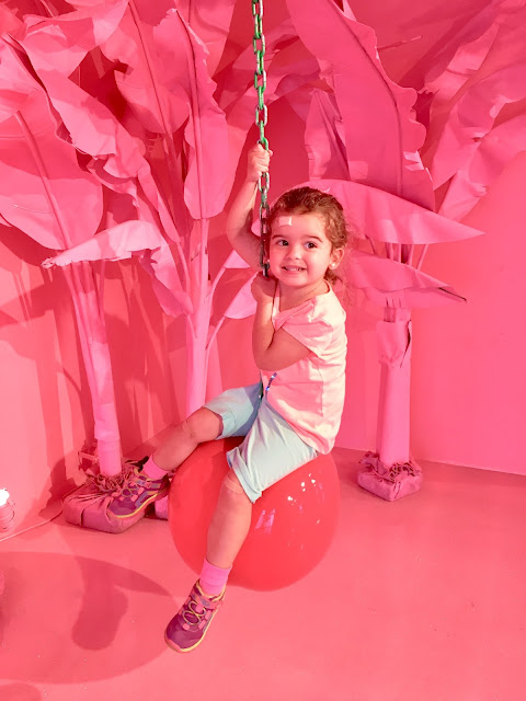 A toddler girl sitting on a cherry wrecking ball