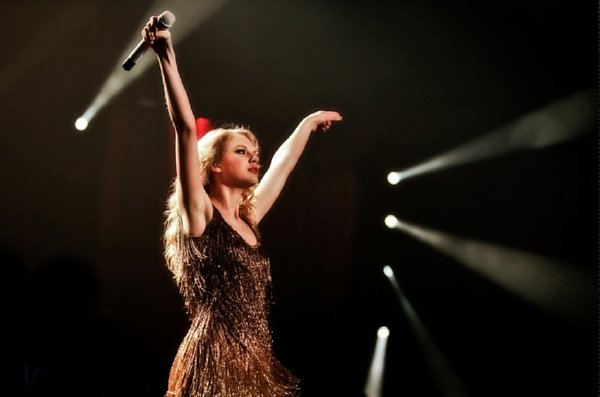 Taylor Swift with both arms raised high on dark stage with spot lights around her