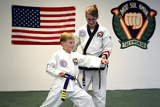 A martial arts woman black belt helps a junior student learn to punch