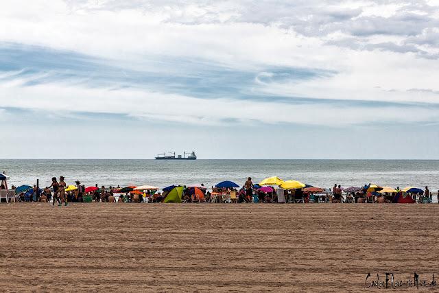 Paisaje  marino con arena,mar nubes y barco en el horizonte