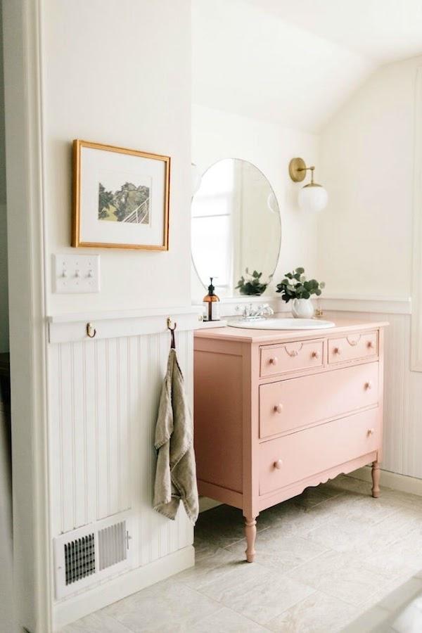 10 ideas para renovar el baño por menos de 100€, baño antiguo con mueble pintado de rosa y detalles en color dorado.