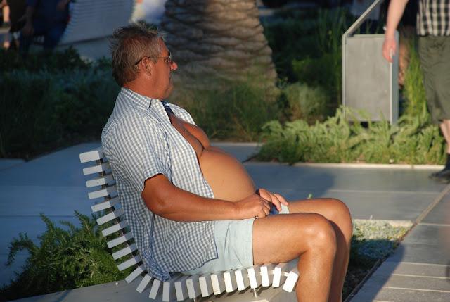 pria perut buncit sedang santai, perut buncit tanda kemakmuran